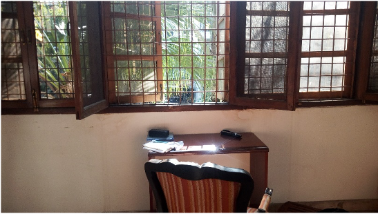 Photo of a desk in front a sunny window in India