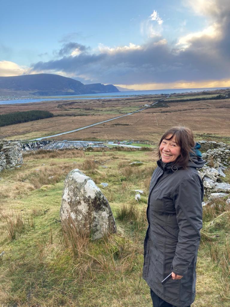 Photo of Eileen standing in a field in Ireland