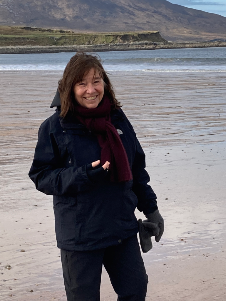 Photo of Eileen smiling on a beach in Ireland