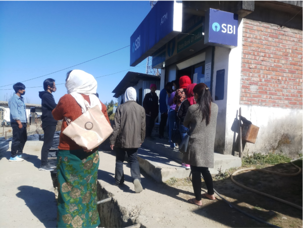 Photo of people waiting outside a bank
