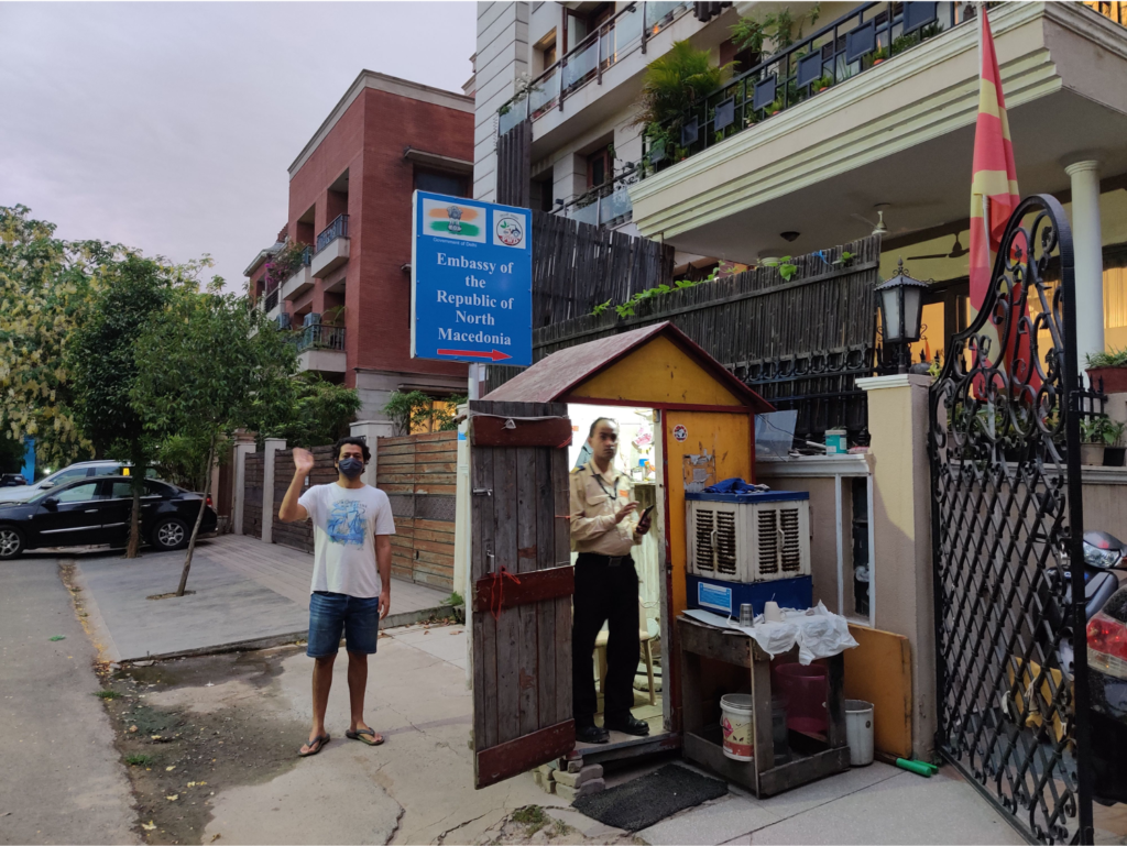 Photo a man in a booth for the Macedonia embassy in India and a man waving at the back of the booth