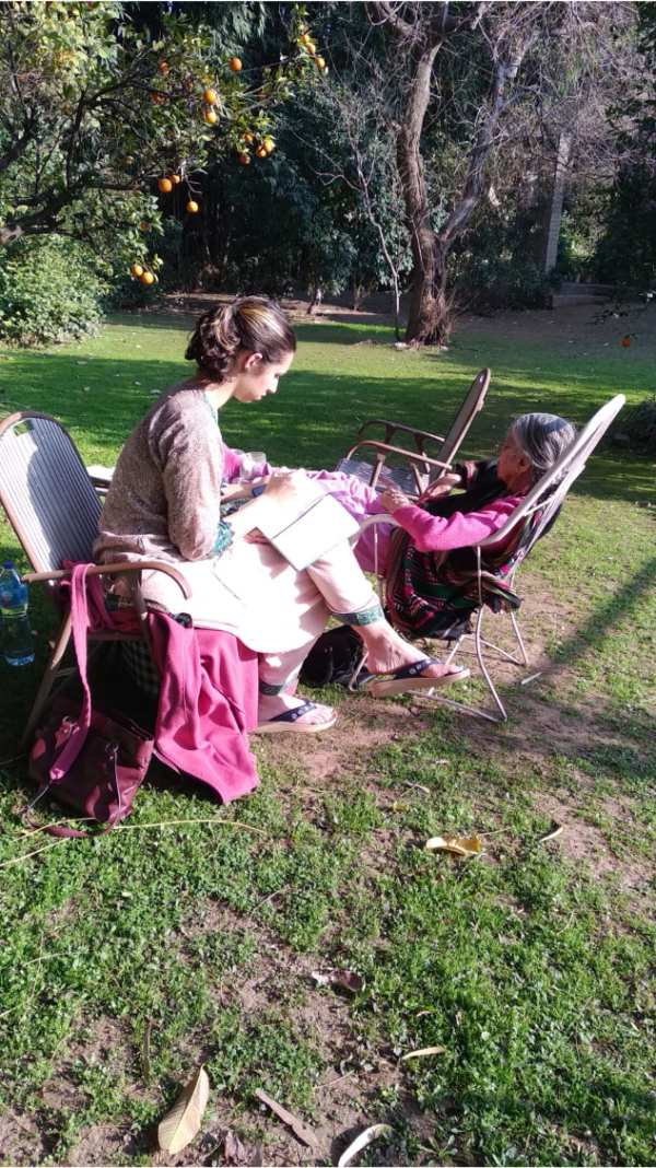 Photo of 2 women sun lounging in a garden in India