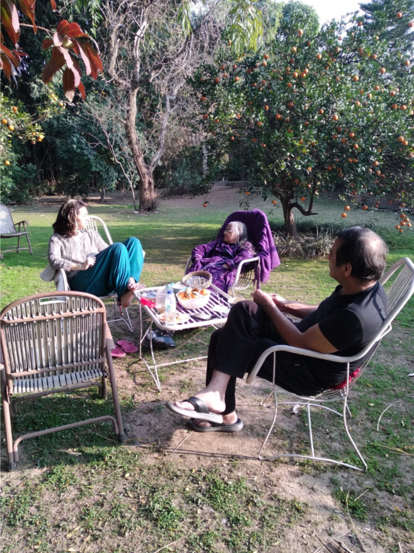 photo of 3 people sun lounging in an Indian garden